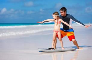 pai e filha praticando surf