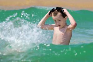 menino brincando no mar foto