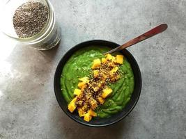 tigela de smoothie verde com sementes de manga e chia picadas