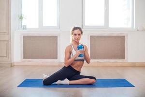linda mulher desportiva atlética, sentado no tapete de ioga depois de alguns foto