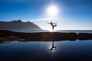 mulher caucasiana está fazendo exercícios de ioga contra pitoresca lan foto