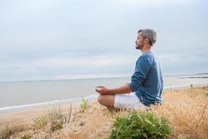 homem atraente está sentado de frente para o oceano foto