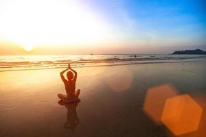 jovem meditando na praia ao pôr do sol. foto