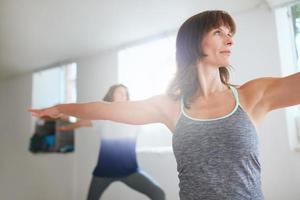 mulheres exercitando na aula de yoga foto