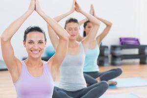 mulheres com as mãos unidas no estúdio de fitness foto