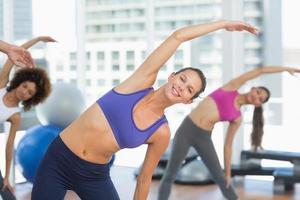 desportivas mulheres esticando as mãos na aula de yoga foto