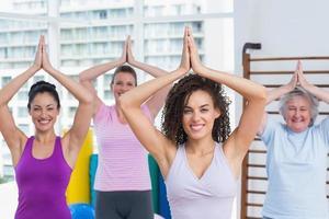 amigos felizes praticando pose de árvore no estúdio de fitness foto