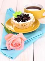 bolo doce com uma xícara de chá em fundo de madeira