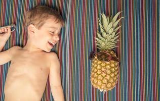 criança feliz e abacaxi tomando banho de sol sobre uma toalha