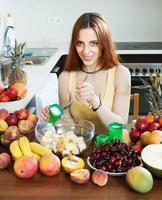 mulher de cabelos compridos positiva cozinhar salada de frutas