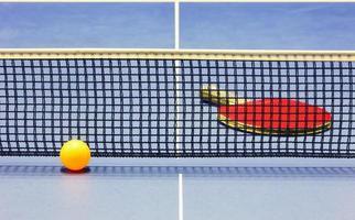 bola de ping pong, raquete e rede na mesa azul