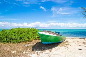 velho barco de pesca em uma praia tropical no Caribe foto