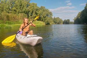 jovem desportivo caiaques no rio enevoado foto