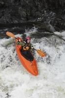 mulher de caiaque no rio foto