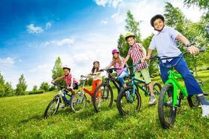 fileira de crianças em capacetes coloridos segurando bicicletas foto
