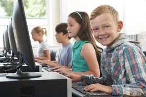 grupo de crianças do ensino fundamental na aula de informática foto