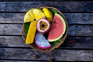 cesta de frutas coloridas da Ásia na mesa de madeira foto