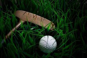 bola de golfe e taco em campo verde foto