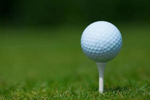 bola de golfe em um tee branco foto