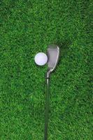 bola de golfe e clube de ferro na grama foto