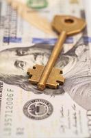 closeup de chave em notas de cem dólares foto