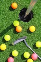 bolas de golfe em torno de um buraco foto
