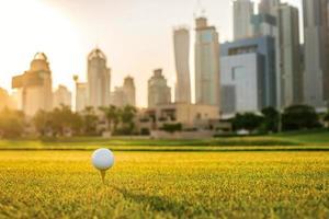jogando golfe ao pôr do sol. bola de golfe está no tee foto
