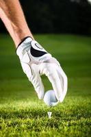 mão segure a bola de golfe com tee no curso foto