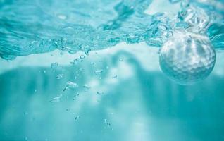 bola de golfe na água para o fundo. foto