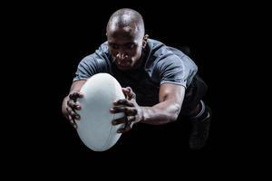 jogador de rugby, pulando enquanto pega a bola foto