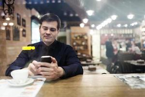 cavalheiro sentado à mesa usando o telefone foto