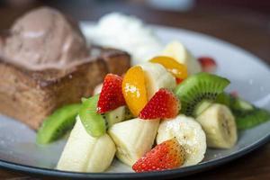 sorvete e salada de frutas amêndoa torradas pão foto