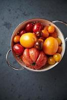 variedades variadas de tomate em uma peneira foto