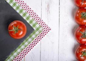 tomates de quadro em fundo branco de madeira foto