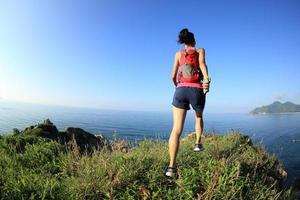 corredor de trilha jovem mulher fitness apreciar a vista foto