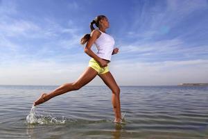 menina de beleza correr na praia foto