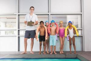 treinador de natação com seus alunos à beira da piscina foto