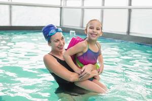 menina bonitinha aprendendo a nadar com o treinador foto