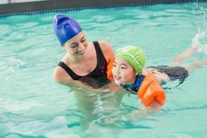 menino bonitinho aprendendo a nadar com o treinador foto