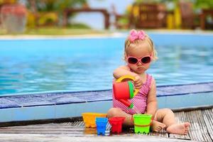 linda garota brincando na piscina na praia tropical foto