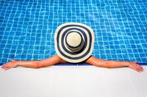 mulher de chapéu de palha relaxante piscina