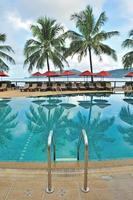 espreguiçadeiras e guarda-sóis à beira da piscina em um resort tropical