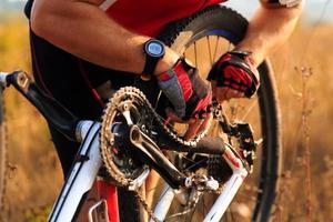 reparação de bicicletas. jovem reparando bicicleta de montanha foto