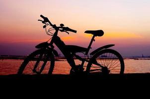 silhueta de bicicleta de montanha com céu pôr do sol foto