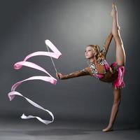 ginasta rítmica fazendo divisão vertical com fita foto