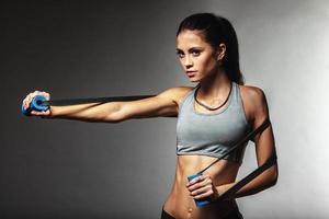 mulher exercitando com fita de borracha foto
