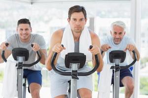 homem com amigos em bicicletas ergométricas foto