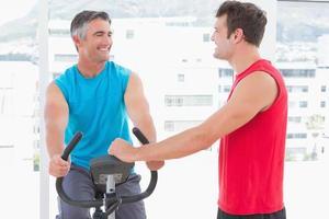 treinador com homem na bicicleta ergométrica foto