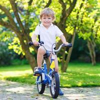 menino pré-escolar feliz andando de sua primeira bicicleta foto