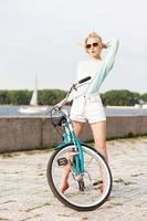 menina bonita com bicicleta da cidade no cais do mar foto